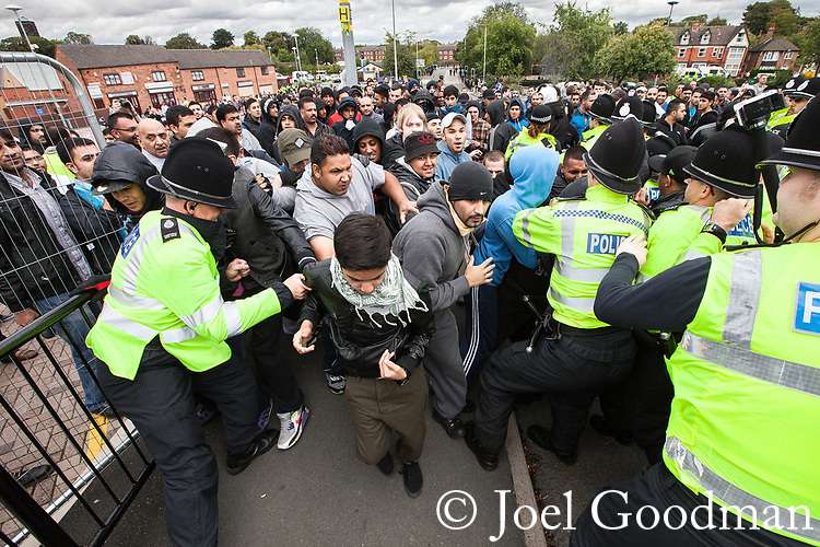 © Joel Goodman - 07973 332324 . 13/08/2011 . Shropshire , UK . Police work to separate counter protesters from EDL supporters . Approximately 300 EDL supporters demonstrate against a paedophile ring in the small Telford town of Wellington . The group had planned to march, however the Home Secretary has imposed a ban on all marches in the area just days after riots have swept across England. A counter-demonstration has attracted about 300 people . Photo credit : Joel Goodman