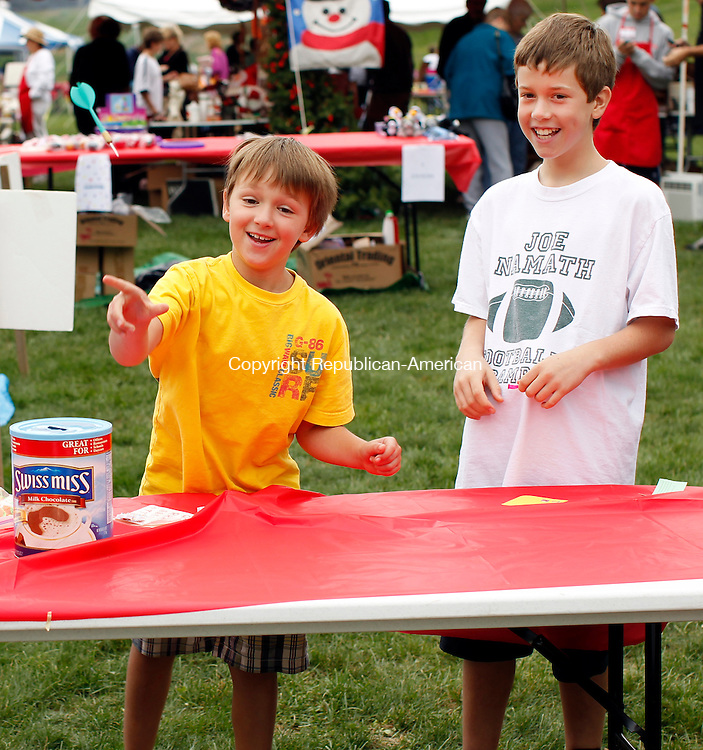 Middlebury, CT- 12, September 2010-091210CM12  Dylan Post, 9 throws a dart as Dean Pope, 11, looks on during the annual Apple Harvest Festival in Middlebury.  Post was trying to pop balloons for a prize.    Christopher Massa Republican-American