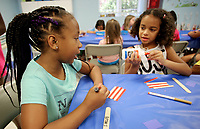 NWA Democrat-Gazette/DAVID GOTTSCHALK  Allison Brooks (left), 8, makes a popsicle stick flag with Brielle Alexander, 7, Monday, July 2, 2018, in the multi purpose room as they participate in the Yvonne Richardson Community Center Summer Camp. Open to students from kindergarten to eighth grade, the eight week long camp offers opportunities to participate in craft projects, water games, indoor activities  and go on field trips.