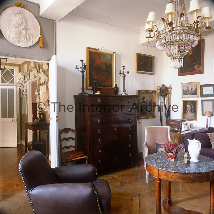A sitting room with a parquet foor. The room is furnished with traditional pieces including a tall chest of drawers and a chandelier.