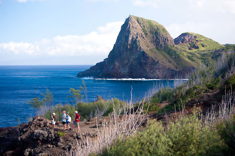 Visitors to the island of Maui looking out at whales off the coast of the North shore of West Maui with Kahakuloa headland in the distance.