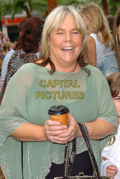 "LINDA ROBSON .At the Uk Premiere of ""Madagascar"",.Odeon Cinema Leicester Square, London, .July 3rd 2005..half length green sheer see through poncho holding drink cup of coffee.Ref: CAN.www.capitalpictures.com.sales@capitalpictures.com.©Can Nguyen/Capital Pictures"