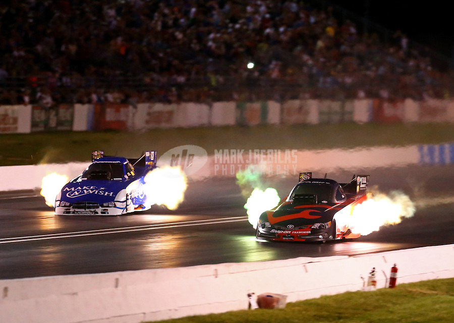May 30, 2014; Englishtown, NJ, USA; NHRA funny car driver Cruz Pedregon (right) runs a 3.959 alongside Tommy Johnson Jr during qualifying for the Summernationals at Raceway Park. The run was the quickest in NHRA funny car history. Mandatory Credit: Mark J. Rebilas-