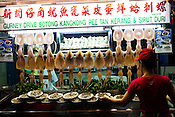 A local takes a plate of shell fish at a Chinese Hawker stall in Gurney Drive, Georgetown in Penang, Malaysia. Photo: Sanjit Das/Panos