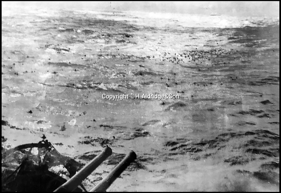 BNPS.co.uk (01202)558833Pic: H.Aldridge&Son/BNPS<br /> <br /> Men floundering in the sea moments after the notorious Bismarck battleship had been destroyed by the Royal Navy in 1941.<br /> <br /> Shocking photographs that show hundreds of German sailors drowning in the wake of the sinking of the fearsome battleship Bismarck have come to light after 77 years.<br /> <br /> The grainy black and white images depict the small black dots of men floundering in the sea moments after the notorious vessel had been destroyed by the Royal Navy in 1941.<br /> <br /> Another image shows some of the survivors doggy paddling beneath the hull HMS Dorsetshire that had taken part in the attack.<br /> <br /> The prints, which measure 10ins by 7ins, have sold at auction for £6,000 - four times the auctioneer's estimate.