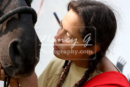 Native American Indian woman bonding with her horse closeup to the nose