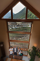 Switzerland. Canton Ticino. Gnosca. The sustainable house built by architect Simone Comandini. The Comandini family stands in the living room. Left to right: Ilan - 15 years old, Simone, Lucia, Nicolas - 13 years old. The structure of the house is made in wooden frame, filled with straw bales and closed by a smooth layer of earth and sand. The construction is based on improving the ecological footprint of the building and for its inhabitants to live in a house with high energy performance. 23.09.17 © 2017 Didier Ruef