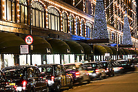 United Kingdom, London, Knightsbridge: Harrods Department Store. Line of taxis outside front of store at Christmas