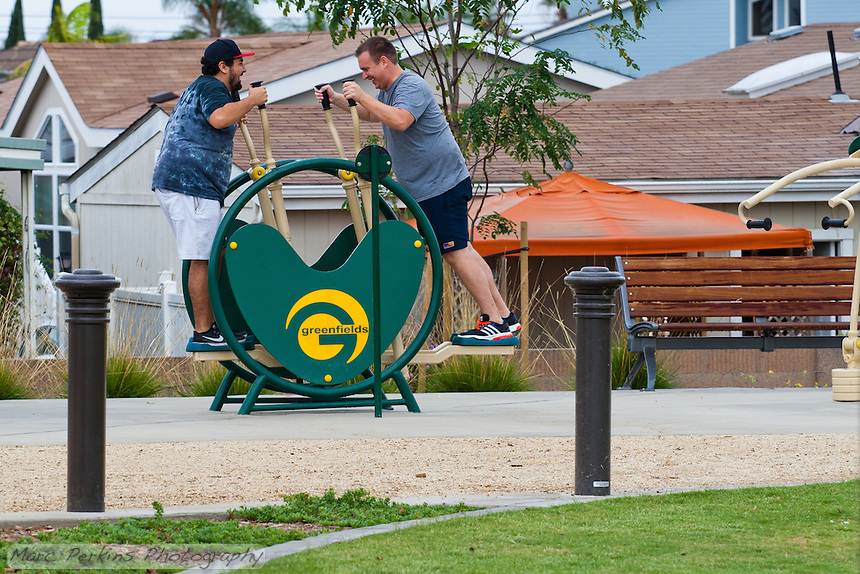 Two men work out on a Greenfields body-weight exercise machine on a cloudy day.  The two men's expressions are of pure glee; the walking path, a bench, and some grass are visible in the foreground.