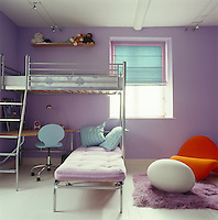 Contemporary metal bunk beds with an incorporated work area are the focal point of this child's bedroom which is painted a pretty lavender