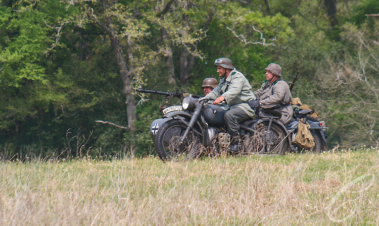Reenactors showcase World War II tanks, half-tracks and support vehicles during the Museum of the America G.I.'s annual Open House on March 29, 2008 in College Station, Texas. Reenactors portraying a German motorized patrol make a dash across the battlefield.