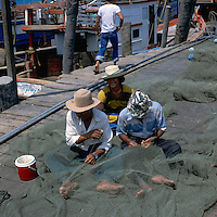 Three fishermen repairing nets. Pattaya beach, Thailand.