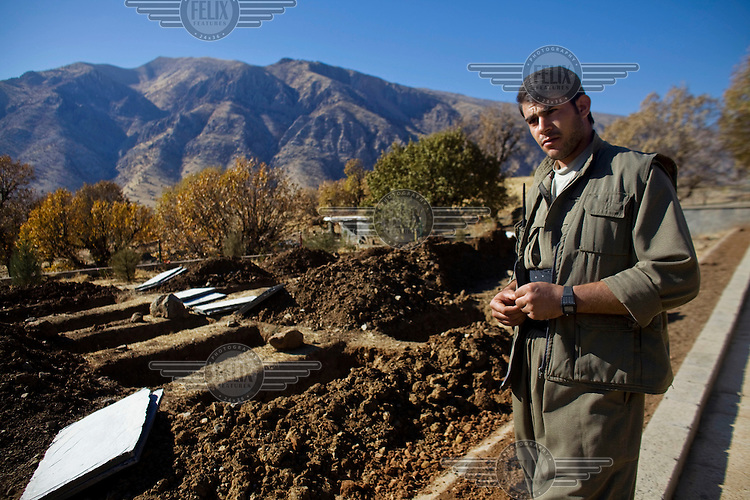 A PKK guerilla and caretaker of Mehmet Karasungur Cemetery stands by new graves. Labelled as terrorists by the Turkish, US and EU, it's in the Qandil Mountains near the border where the guerrillas of the PKK (Kurdistan Worker's Party) live and wage their 26 year war against Turkey that has claimed over 40,000 lives. According to a PKK spokesperson, the hospital was named after a patient who was killed in Turkish bombardment at a nearby hospital.