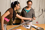 Education High School physics science lab two female students working together setting up experiment on rolled marble trajectory