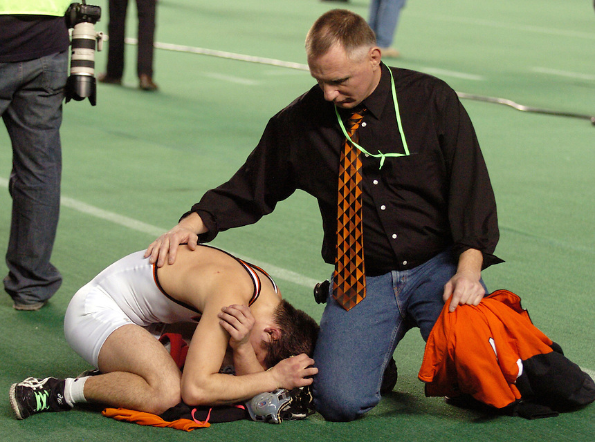 Blaine head coach Craig Foster comforts Blaineís Jacob Humphrey after Humphrey lost to Black Hillsí Nick Burnham the a 119-pound 2A championship match  during the 2008 Mat Classic XX wrestling state championship at the Tacoma Dome on Saturday, February 16, 2007. Humphrey won second place.