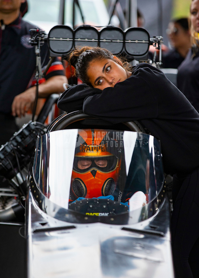 May 20, 2018; Topeka, KS, USA; Jasmine Salinas daughter of NHRA top fuel driver Mike Salinas leans against the car as her father sleeps inside during a delay to the Heartland Nationals at Heartland Motorsports Park. Mandatory Credit: Mark J. Rebilas-USA TODAY Sports