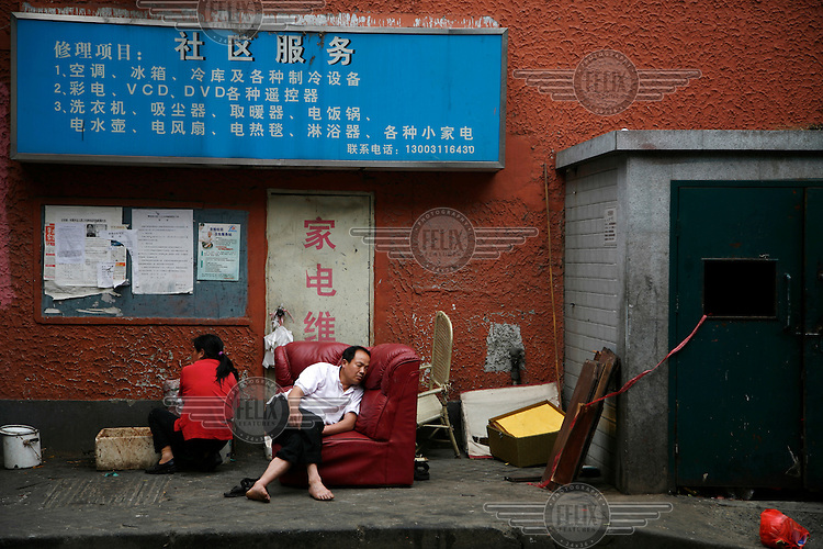 A man takes a nap on a street-side couch in Shanghai.