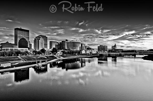 Dayton Ohio Skyline black and white with geese flying over a calm river