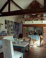 An Aga is situated in the large fireplace at one end of the cosy kitchen where a large collection of family photographs is displayed