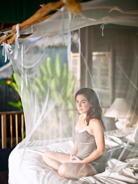 A woman enjoys morning sunlight and an ocean view inside a mosquito net at the Masters Bedroom of the Hilltop Reserve, a three-bedroom private pool villa at Six Senses Hideaway Yao Noi. Thailand.