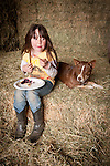 Tori Joses and her dog Zoe sit on the bales of hay and eat berry pie in the Guttenger Barn, San Andreas, Calif.