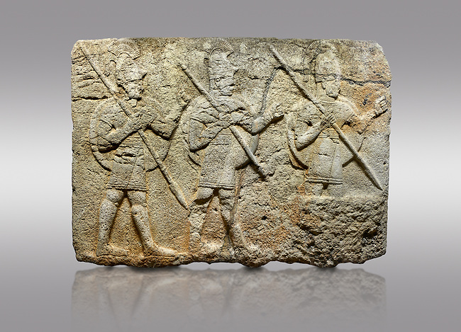Picture & image of Hittite monumental relief sculpted orthostat stone panel from the Herald's Wall. Basalt, Karkamıs, (Kargamıs), Carchemish (Karkemish), 900-700 B.C. Military parade. Anatolian Civilisations Museum, Ankara, Turkey. Two helmeted soldiers in short skirts carry the shield on their backs and the spears in their hands.  <br /> <br /> Against a gray background.
