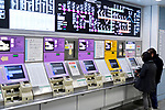 People buying train tickets from a subway station ticket machine, vending kiosk at a train station in Kyoto, Japan 2017