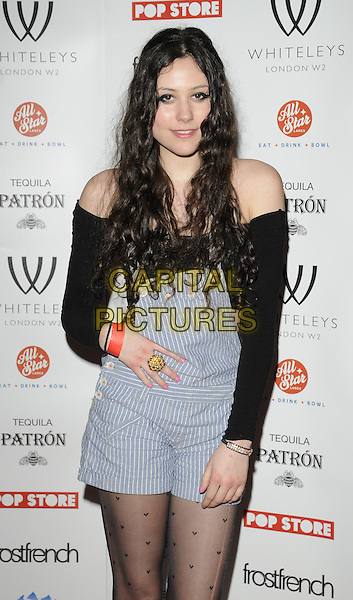 ELIZA DOOLITTLE.The Whiteleys Pop-Up Boutique Floor launch party, Whiteleys Shopping Centre, Queensway, London, England..March 25th, 2010.half length black off the shoulder top pattern tights blue striped stripes dungarees overalls shorts romper playsuit hand on hip gold ring pink nail varnish polish.CAP/CAN.©Can Nguyen/Capital Pictures.