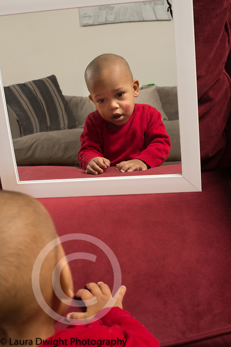 18 month old toddler boy looking at self in mirror lipstick spot on cheek rouge test for self recognition