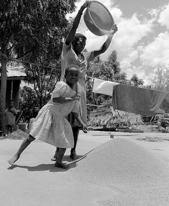 Young girl and her mother wind blowing sorgum grain in a village. West Nile Uganda