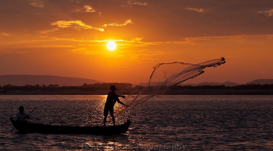 Fisherman casting his net on the Ayeyarwady river at sunset
