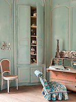 A detail of a traditional reception room decorated in turquoise with white mouldings. A chair in blue and white floral pattern is placed at a writing bureau. The colour scheme and furniture lend the room a Scandinavian feel.