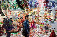 November 28, 2015, Yiwu China - Potential customers examine cheap Christmas decorations inside  a booth in the Festival Arts section of the Yiwu International Trade Market. Yiwu International Trade Market is the world's largest whole sale market for small commodities. Christmas decorations are available for bulk purchase all the year round.Photo by Dave Tacon / Sinopix