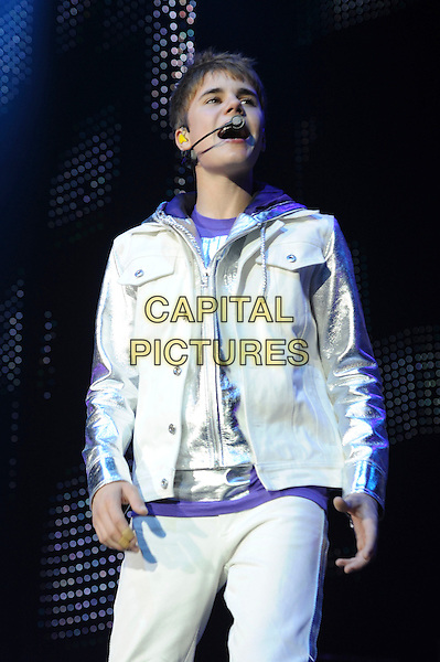 JUSTIN BIEBER.performing at the O2 Arena, North Greenwich, London, England, UK,.14th March 2011..half length white hoodie hood singing music concert on stage gig  silver microphone eyes shut closed 3/4  .CAP/WIZ.© Wizard/Capital Pictures.