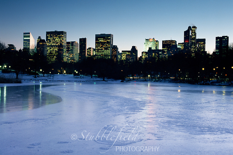 Midtown Manhattan as seen from the frozen lake in New York's Central Park on a cold winter evening.