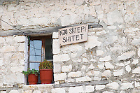 Traditional ottoman white stone house. A sign on the house saying that the house is for sale. Berat upper citadel old walled city. Albania, Balkan, Europe.