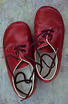 Pair of young childs lace-up red shoes shiny but slightly scuffed lying on marbled slate