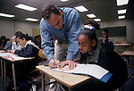 Oakland CA Young seventh-eighth grade teacher helping student work out problem with protractor