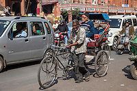 Jaipur, Rajasthan, India.  Mid-day Street Traffic in Central Jaipur.  Rickshaw Driver Walks his Rickshaw through Conjested Traffic.