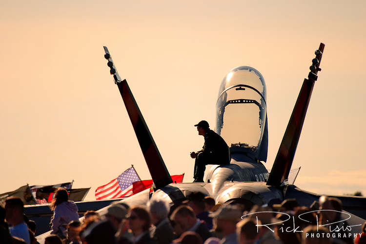 United States Navy pilot sits atop an F/A-18 Hornet during an air show.