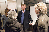 "Dan Dorman, NRC Region 1 Regional Administrator, (center) speaks with people after a public hearing regarding Pilgrim Station, a nuclear power plant run by Entergy, at Hotel 1620 in Plymouth, Massachusetts, USA, on Tues., Jan. 31, 2017. An email from the NRC was leaked in December 2016 outlining problems with the ""safety culture"" at the plant and an ""overwhelmed"" staff. Area residents have been calling for the plant to be shut down. The green signs in the audience, reading ""Shut Pilgrim Now,"" are from a group of area residents calling for the plant's closure called Cape Downwinders."