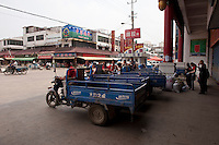 Daytime landscape view of a line of motorized tricycles parked on a road in front of the Chinese Herbal Medicinal Market in Bozhou in Qiáochéng Qū in Anhui Province.  © LAN