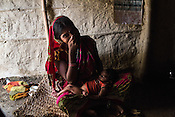 25 year old Srikanthi Devi poses for a photograph her 3 months old son in the kitchen of their house in Ramgarwa village in Raxaul district in Bihar, India.