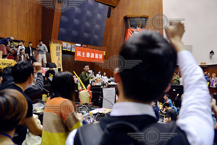 "Student leader Lin Fei-Fan (centre) addresses the amassed students and some of the local press inside Taiwan's Legislative Yuan (Parliament) Building on the 4th day of its occupation by students in opposition to the passing of the Cross-Straight Service and Trade Agreement between Taiwan and China.  The students, and many normal Taiwanese, fear the erosion of their hard-won democracy and, eventually, independence, making them, in the words of one student protestor 'no better off than Hong Kong'. Ma ying-jeoh bears the brunt of the protestors ire; known as ""Ma 9%"" after his latest approval rating, he is seen as kowtowing to the demands of China and selling out Taiwan."