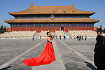 a model poses in a red gown outside of the sacrificial temple in the Forbidden City, Beijing, China