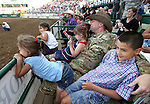 Nevada Army National Guard Chief Warrant Officer Glen Spadin watches the rodeo action with his children after his surprise return from Afghanistan during Patriot Night ceremonies at the Reno Rodeo in Reno, Nev. on Friday, June 19, 2015. Spadin returned after a year in Afghanistan to surprise his six children.<br /> Photo by Cathleen Allison