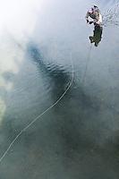 A fly fisherman strips a streamer beneath a bridge in northern Montana.