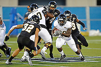 30 March 2012:  FIU's Shane Coleman (20) carries the ball while being pursued by Richard Leonard (3) and Justin Halley (32) at the FIU Football Spring Game at University Park Stadium in Miami, Florida.