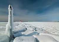 A pier entrance light and athe pier itself are cobered with ice born of wave spray on the Muskegon North Pier with the light on the distant end having shed its ice from from its red color and solar warmth, Muskegon, Michigan