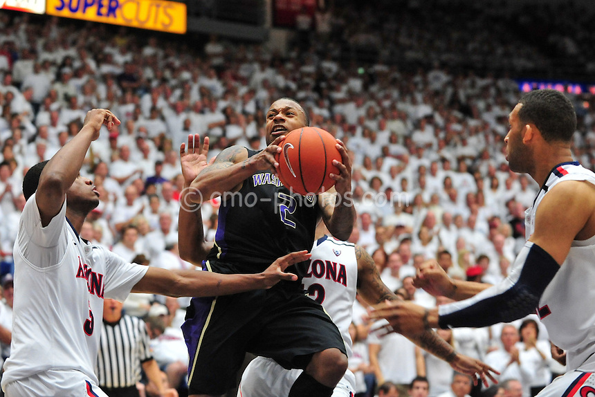 Feb 19, 2011; Tucson, AZ, USA; Washington Huskies guard Isaiah Thomas (2) is surrounded by three Arizona Wildcats defenders as he goes up to shoot in the 2nd half of a game at the McKale Center.  The Wildcats won 87-86.